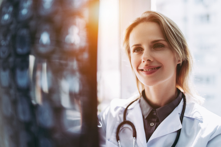 Experianced female doctor in clinic is examining the X-ray image. Roentgen Stock Photo