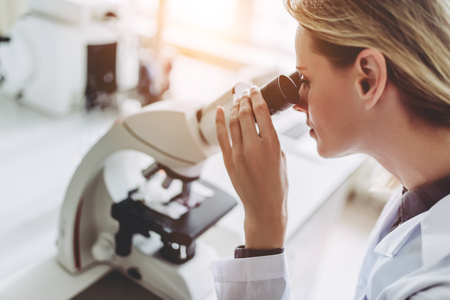 Experienced female scientist is working in laboratory. Doing investigations with microscope. Stock Photo