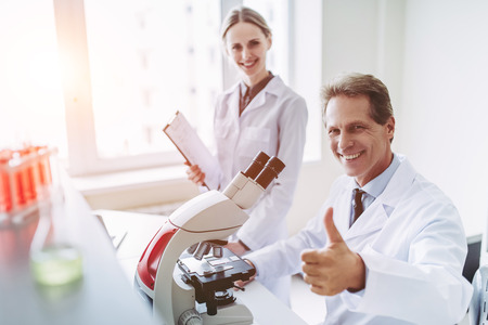 Two scientists are working in laboratory. Young female researcher and her senior supervisor are doing investigations with microscope, smiling, looking at camera and showing thumb up.