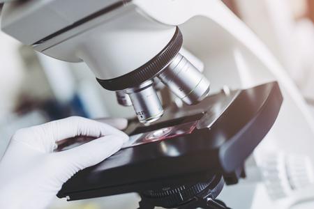 A imagem do close-up do cientista do laboratório está trabalhando com microscópio. Fazendo uma investigação no laboratório. Foto de archivo