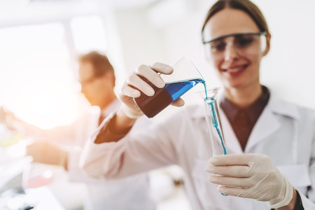 Two scientists are working in laboratory. Young female researcher and her senior supervisor are doing investigations with test tubes.