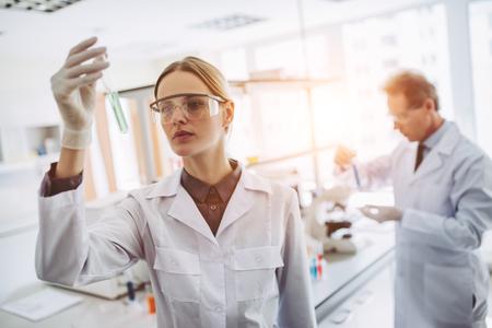 Dwóch naukowców pracuje w laboratorium. Młoda badaczka i jej starszy przełożony prowadzą badania z probówkami.