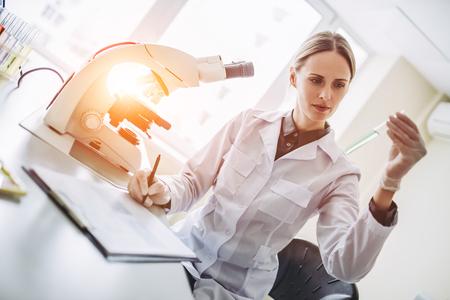Experiente cientista feminina está trabalhando em laboratório. Fazendo investigações com microscópio e tubos de ensaio. Foto de archivo