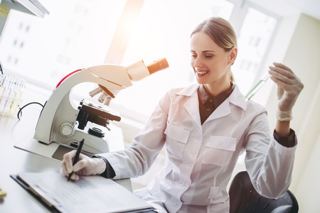 Experienced female scientist is working in laboratory. Doing investigations with microscope and test tubes.