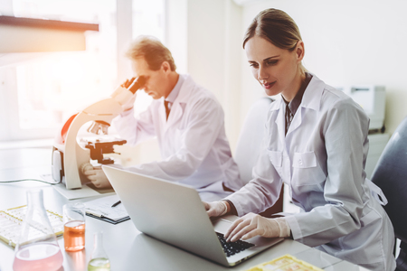 Two scientists are working in laboratory. Young female researcher and her senior supervisor are doing investigations with microscope and laptop. Archivio Fotografico