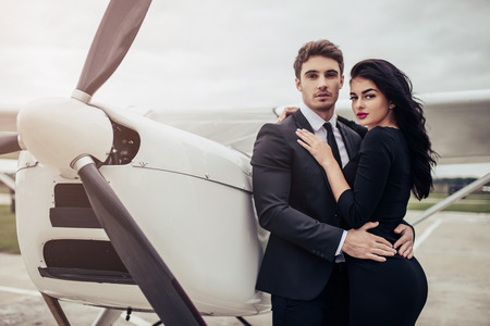 Beautiful young stylish couple in official clothes is standing near private plane. Hugging and kissing in airport in front of airplane. Stockfoto