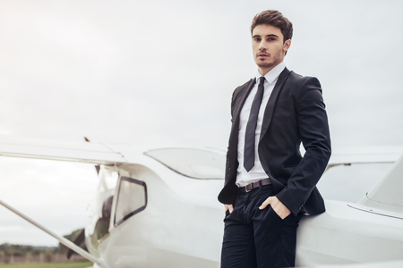 Young handsome businessman is standing near private plane. Confident and successful man in airport. Reklamní fotografie