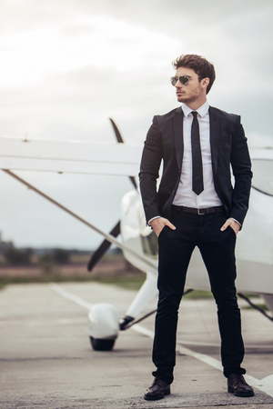 Young handsome businessman is standing near private plane. Confident and successful man in airport. Stock Photo