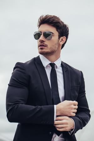 若いハンサムなビジネスマンの肖像画は、公式の服とサングラスで立っています。スーツに自信と成功した男。