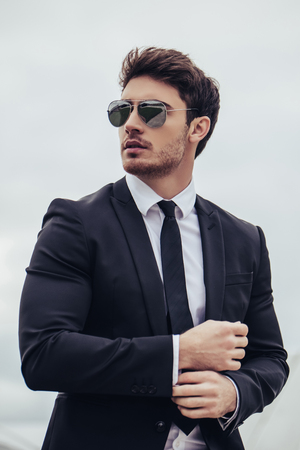 Portrait of young handsome businessman is standing in official clothes and sunglasses. Confident and successful man in suit. Foto de archivo