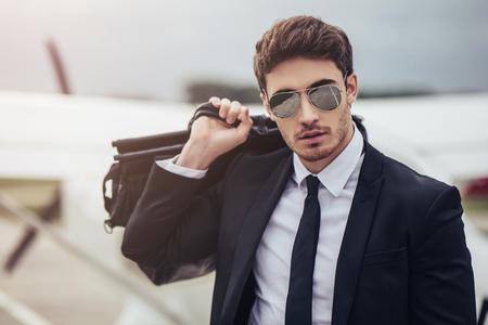 젊은 잘 생긴 사업가 개인 비행기 근처에 서있다. 공항에서 자신감과 성공적인 사람입니다.