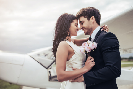 Just married! Beautiful young romantic couple is hugging and kissing near private plane. Attractive woman in wedding dress and handsome man in suit are celebrating wedding day in airport near airplane. Ready for Honeymoon.