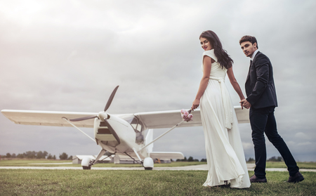 Just married! Beautiful young romantic couple is standing near private plane. Attractive woman in wedding dress and handsome man in suit are celebrating wedding day in airport near airplane. Ready for Honeymoon.
