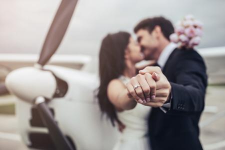 Net getrouwd! Het mooie jonge romantische paar bevindt zich dichtbij privé vliegtuig. De aantrekkelijke vrouw in huwelijkskleding en de knappe man in kostuum vieren huwelijksdag in luchthaven dichtbij vliegtuig. Klaar voor huwelijksreis. Jonge vrouw toont trouwring. Stockfoto
