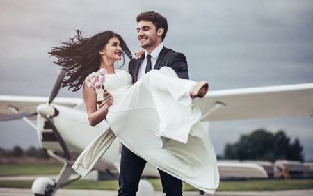 Just married! Beautiful young romantic couple is dancing near private plane. Attractive woman in wedding dress and handsome man in suit are celebrating wedding day in airport near airplane. Ready for Honeymoon.