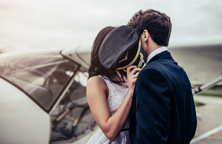 Young handsome man pilot in uniform is standing near small private plane with his beautiful young woman. Couple is hugging and kissing on runway near airplane. Stok Fotoğraf