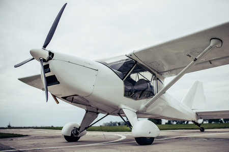 Light propeller airplane on runway. Small private fix-wing plane. Stock Photo