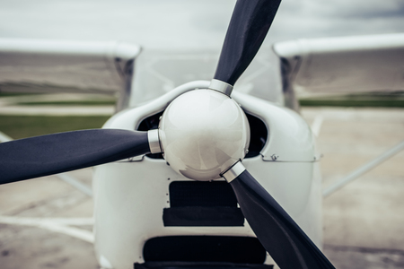 Light propeller airplane on runway. Small private fix-wing plane. Close-up of propeller.