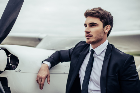 De jonge knappe zakenman bevindt zich dichtbij privé vliegtuig. Zelfverzekerde en succesvolle man in luchthaven.