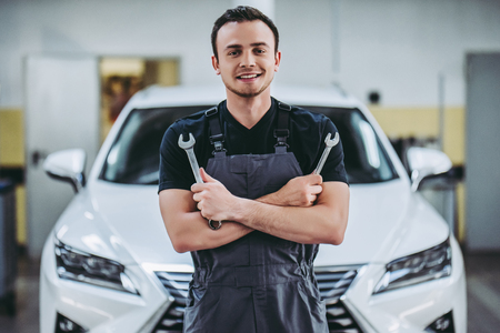 Handsome auto service mechanic in uniform is standing on the background of car with open hood with wrench in hands. Car repair and maintenance.