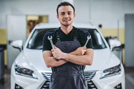 Hübscher Selbstservice-Mechaniker in der Uniform steht auf dem Hintergrund des Autos mit offener Haube mit Schlüssel in den Händen. Autoreparatur und Wartung. Standard-Bild
