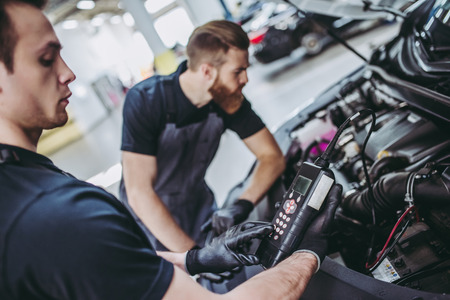 Two handsome mechanics in uniform are working in auto service. Car repair and maintenance. Performing engine diagnostics