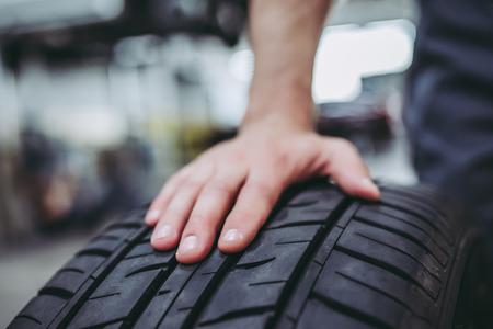 Geerntetes Bild des hübschen Mechanikers in der Uniform arbeitet im Selbstservice. Autoreparatur und Wartung. Auto Rad / Reifen halten. Standard-Bild