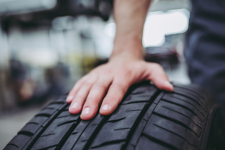 Przycięty obraz przystojnego mechanika w mundurze pracuje w serwisie samochodowym. Naprawa i konserwacja samochodu. Trzymanie koła / opony samochodowej. Zdjęcie Seryjne