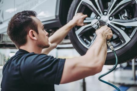 制服姿のハンサムな整備士がオートサービスで働いています。車の修理とメンテナンス。車輪のねじれねじれないボルト。 写真素材