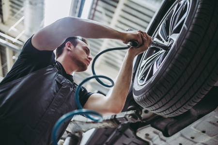 Handsome mechanic in uniform is working in auto service. Car repair and maintenance. Twistinguntwisting bolts on wheel.