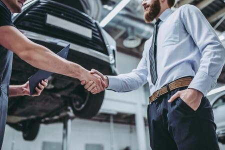 De knappe zakenman en de autodienstwerktuigkundige bespreken het werk en schudden handen. Auto reparatie en onderhoud.