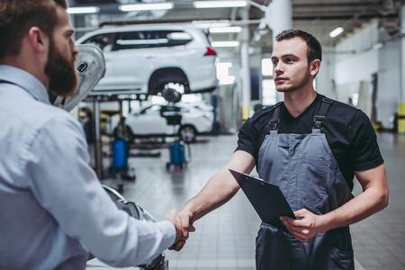 Bel homme d'affaires et mécanicien de service automobile discutent du travail et se serrent la main. Réparation et entretien de voiture. Banque d'images - 92244845