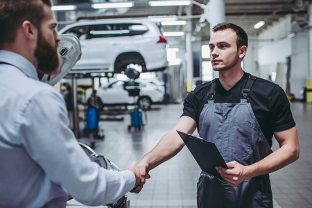 Handsome businessman and auto service mechanic are discussing the work and shaking hands. Car repair and maintenance. Archivio Fotografico