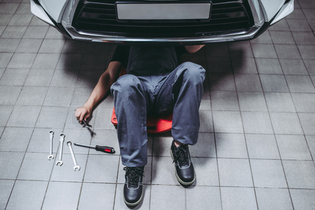 Handsome mechanic in uniform is working in auto service with wrenches. Man on portable plastic repair creeper. Car repair and maintenance. Stockfoto