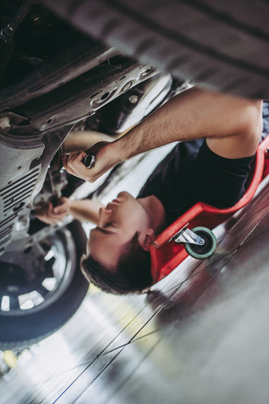 Handsome mechanic in uniform is working in auto service with wrenches. Man on portable plastic repair creeper. Car repair and maintenance. Archivio Fotografico