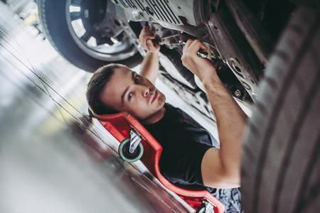 Hübscher Mechaniker in der Uniform arbeitet im Selbstservice mit Schlüsseln. Mann auf tragbarer Plastikreparaturkriechpflanze. Autoreparatur und Wartung.
