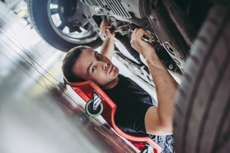 Handsome mechanic in uniform is working in auto service with wrenches. Man on portable plastic repair creeper. Car repair and maintenance. Stock Photo