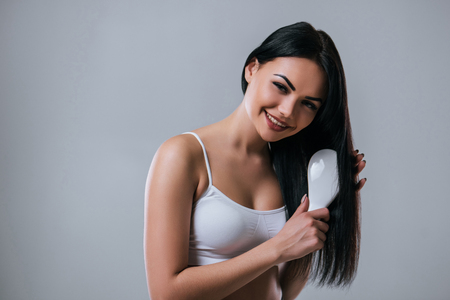 Portrait of attractive young woman is combing out her hair on grey background. Women care