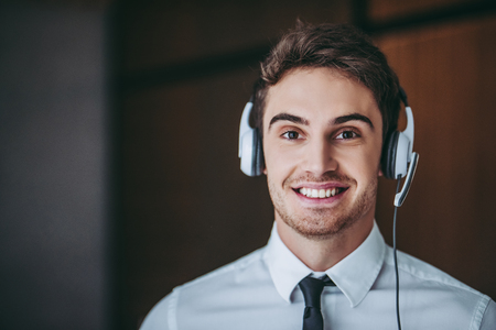 How can I help you?Portrait of handsome male call center worker in headphones smiling and looking at camera.