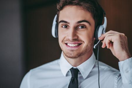 어떻게 도와 드릴까요? 미소하고 카메라를 찾고 헤드폰 잘 생긴 남자가 전화 센터 직원의 세로.