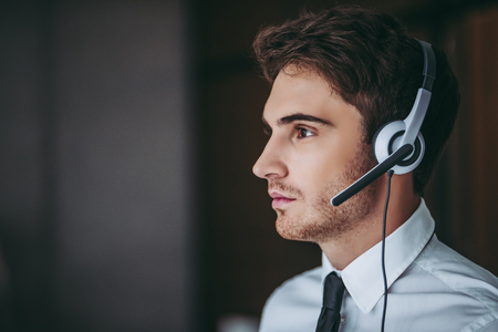 How can I help you?Portrait of handsome male call center worker in headphones is looking to the side. Stock fotó - 92364471
