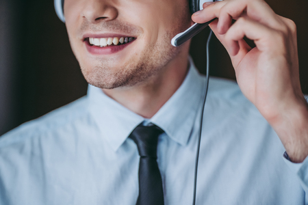 How can I help you?Cropped image of handsome male call center worker in headphones smiling. Stock Photo