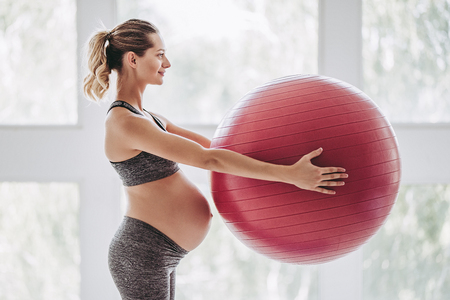 Beautiful pregnant woman workout. Yoga with fitball. Doing fitness on last months of pregnancy.