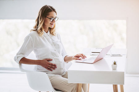 Attractive pregnant woman is working with laptop in light modern office. Last months of pregnancy.