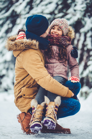 Handsome young dad and his little cute daughter are having fun outdoor in winter. Enjoying spending time together. Family concept.
