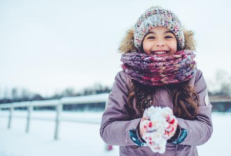 Little cute girl is having fun outdoots in winter.