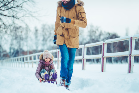 Handsome young dad and his little cute daughter are having fun outdoor in winter. Enjoying spending time together while riding on a sled. Family concept. Stock Photo