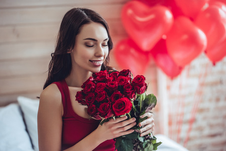 家で美しい若い女性。魅力的な女の子は、ギフトボックス、ハートと赤いバラの形をしたエアバルーンとベッドに座っています。聖バレンタインデ