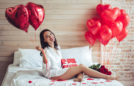 Beautiful young woman at home. Attractive girl is sitting on bed with gift box, air baloons in shape of heart and red roses. Celebrating Saint Valentines Day.