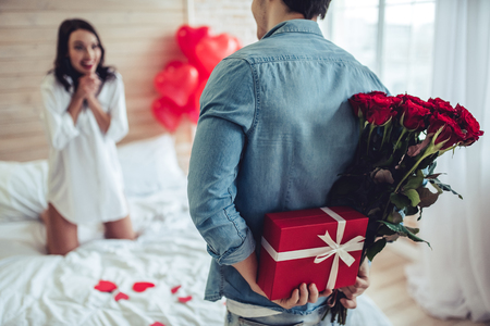 Beautiful young couple in bedroom. Celebrating Saint Valentines Day with gift box, air baloons in shape of heart and red roses. Stok Fotoğraf
